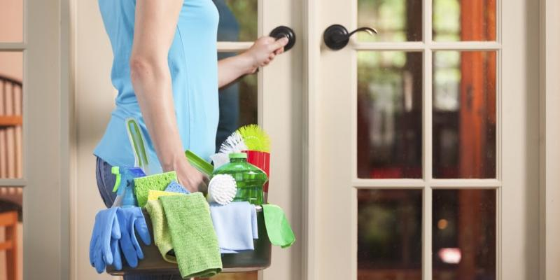 Woman opening door with cleaning supplies in hand. Interstate Pest Management serving Portland OR & Vancouver WA talks about DIY Pest Control Myths.
